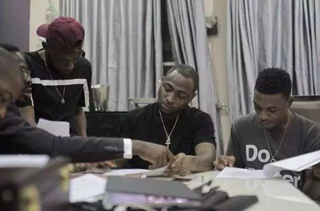 Paper works: L-R Dremo, Davido and Mayorkun during their contract signing