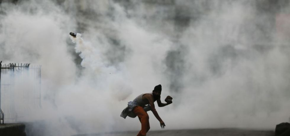 A Kashmiri demonstrator throws a tear smoke shell on government forces to protest against the Sunday's killing of a young man in Srinagar, Indian-controlled Kashmir.