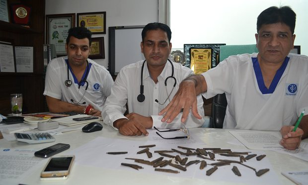 The surgical team with some of the knives removed from the stomach of the police officer
