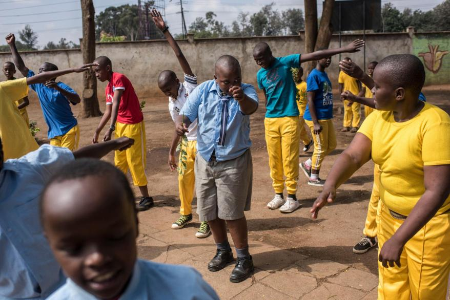 Samuel, 13, center, the son of Fraciah Wangari, exercising during a physical education class at Muthaiga Primary School in Nairobi. He is teased about his weight.