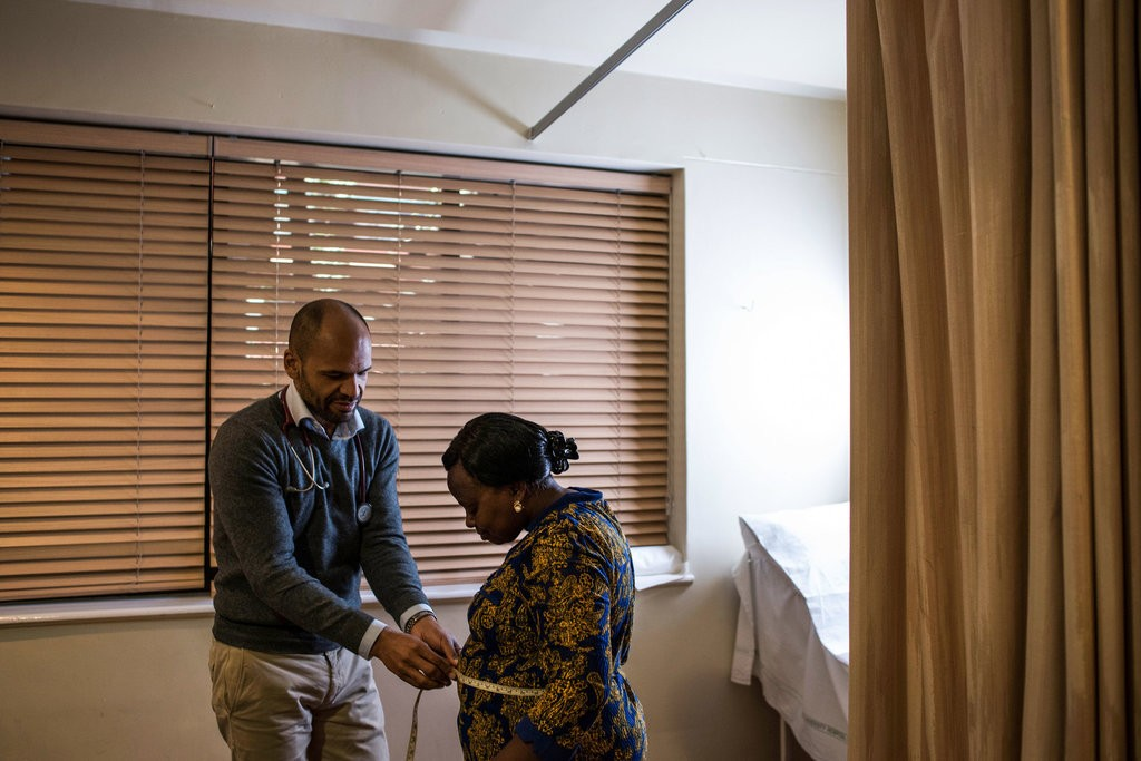 Dr. Anders Barasa, a cardiologist, measures a patient's waistline during an appointment at the heart clinic at Aga Khan University Hospital in Nairobi