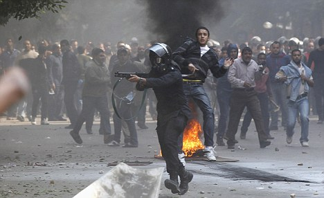 A riot policeman aims a shotgun with rubber bullets at protesters, next to a plainclothes policeman during clashes in a side street near Tahrir Square in Cairo
