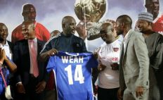 Liberia's President George Weah receives the number 14 shirt he wore at the peak of his football career. He played in a friendly against Nigeria on Tuesday. The match was arranged to mark the retirement of the jersey. Nigeria won 2-1.