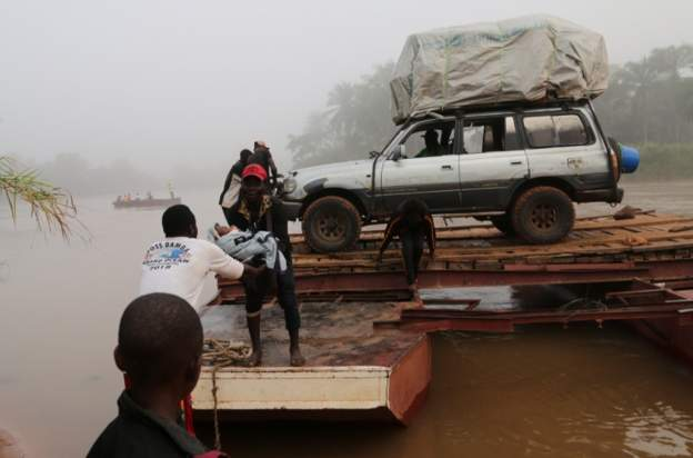 Migrants expelled from Angola cross a river on the road to DR Congo. Photo: Reuters
