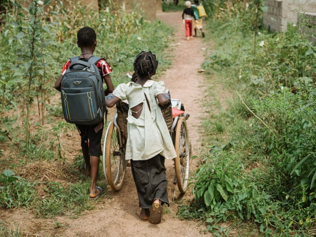 Wendkouni escorts her sister to and from school