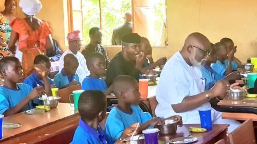 Osinbajo eating in the school