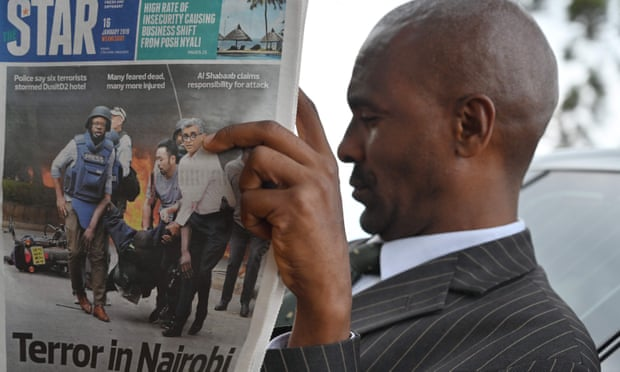A man reads the Star newspaper during the funeral of a victim of this week's attack on a Nairobi luxury hotel complex, at the Langata Muslim cemetery in Nairobi.