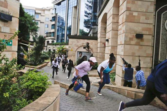Civilians run for safety as police provide cover during the suicide bombing and mass shooting attack on the 14 Riverside complex. Wikimedia