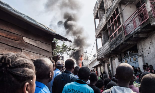 Residents look on as smoke rises after the plane crash in Goma, Democratic Republic of Congo.