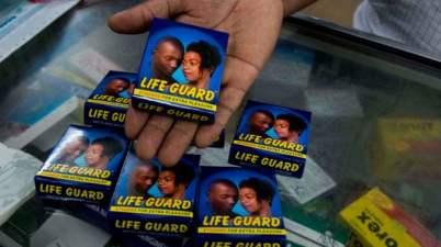 A pharmacist displays a pack of Life Guard condoms at a store in the Ugandan capital Kampala. Photograph: Isaac Kasamani/AFP via Getty Images