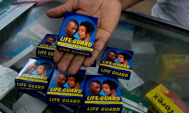A pharmacist displays a pack of Life Guard condoms at a store in the Ugandan capital Kampala. Photograph: Isaac Kasamani/AFP via Getty Images