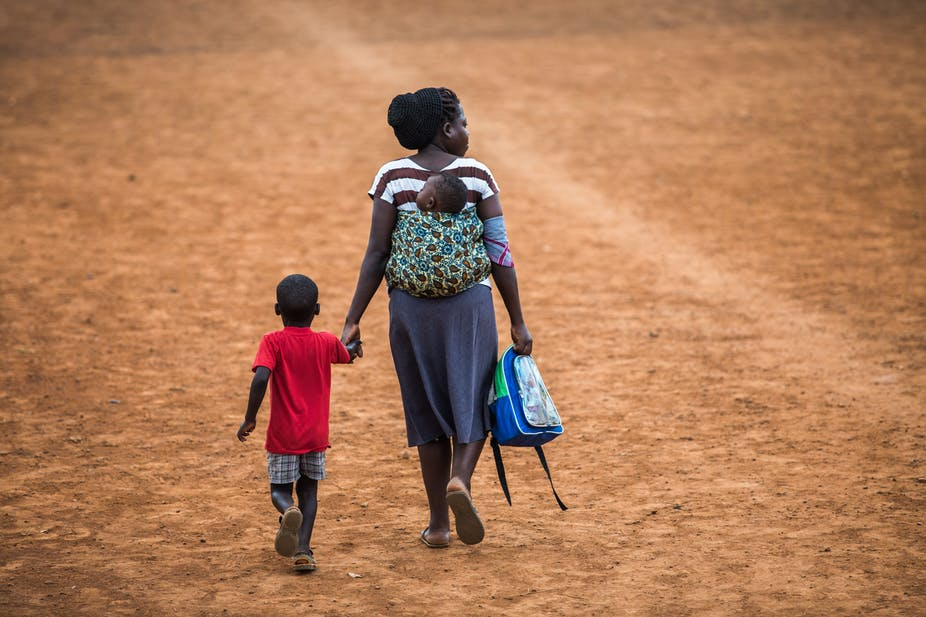 A mother walking her child home from school in Uganda. Shutterstock
