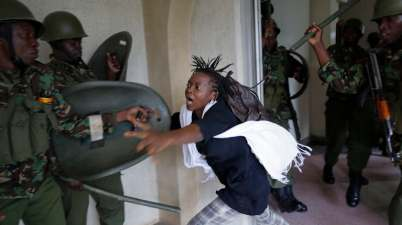A woman flees as a riot police officer beats her with a baton during a protest over fees at the University of Nairobi. EPA/Dai Kurokawa