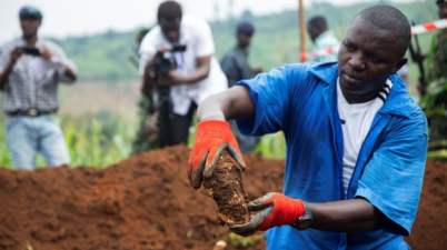 A Burundian worker from the Truth and Reconciliation Commission at the mass grave in Karusi province. Photograph: Evrard Ngendakumana/Reuters