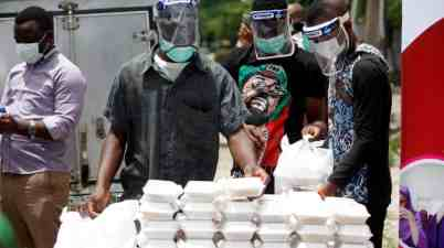Volunteers wearing face shields distribute food in Lagos, Nigeria, where improving the level of testing has been difficult. Photograph: Akintunde Akinleye/EPA